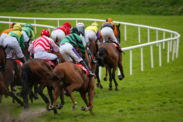 View from behind of galloping race horses and jockeys racing down the track