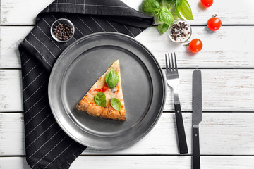 Composition with piece of delicious pizza Margherita on wooden background