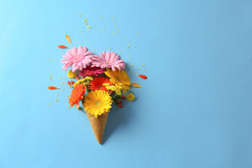 Waffle cone with beautiful flowers on color background
