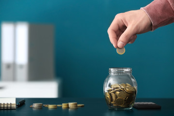 Man putting coins into glass jar on table. Savings concept
