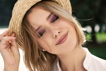 Portrait of smiling woman in sunhat looking at camera