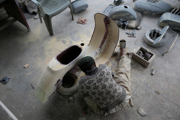 A worker restores parts at a Vespa repair shop in Islamabad