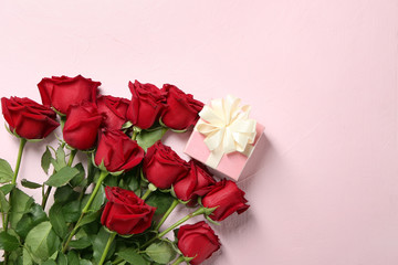 Beautiful roses and gift box on light background