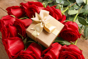Beautiful roses and gift box on wooden table