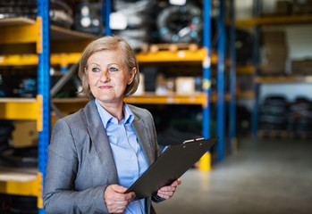 Senior woman warehouse manager or supervisor with clipboard.