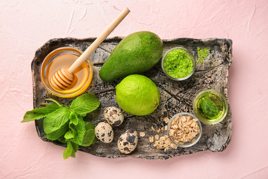 Plate with avocado and ingredients for natural homemade cosmetics on color background