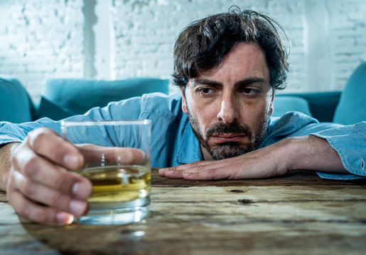 latin businessman drunk and depressed at home in alcoholic concept