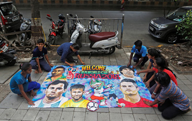 Art school students arrange a mural made for the upcoming FIFA World Cup on a street in Mumbai