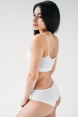 young attractive mixed race womanl in white lingerie isolated on gray background