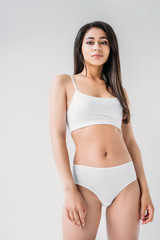 young mixed race woman in white lingerie posing isolated on gray background