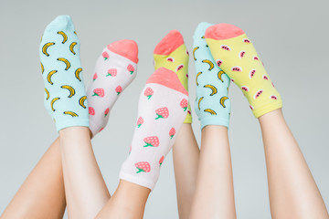 partial view of female feet in colorful fruity socks, isolated on grey
