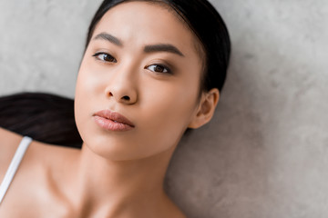 portrait of lovely asian girl looking at camera, on grey