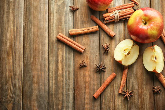 Composition with fresh apples and cinnamon on wooden background