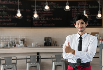 Waiter standing in front of coffee shop, ready for serving.