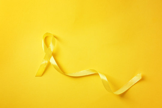 Yellow ribbon on color background. Cancer concept