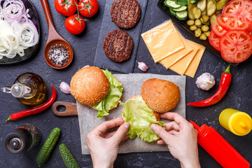 Photo on top of two hamburgers, human hands and ingredients