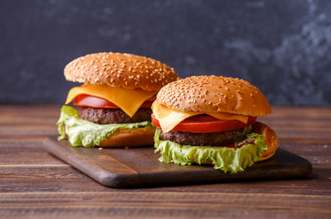 Photo of two hamburgers on a wooden table