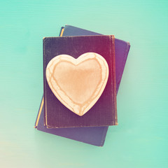 Top view of old books with wooden heart.
