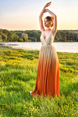 Woman in a long glamorous dress at sunset. Girl lovely gradient dress. Beautiful landscape view. Summer hot Fashions