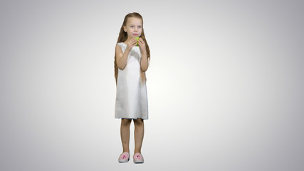 Little girl with green apple, eating it on white background