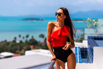 luxury beautiful girl in a branded swimsuit and glasses, in an expensive hotel on a tropical island, against a background of azure sea bay, on the terrace private infinity pool