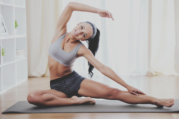 Beautiful girl engaged in yoga at home on gym mat