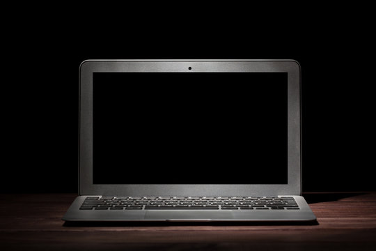 One silver modern laptop on wooden table in a dark room on black background. Nice mockup for your IT project. Dramatic light.
