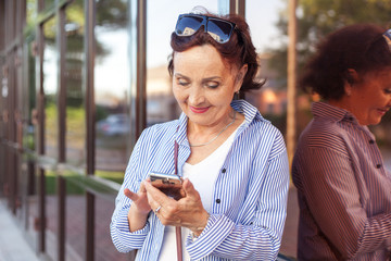 Mature attractive stylish woman retired using mobile phone app for smartphone outdoors on summer day
