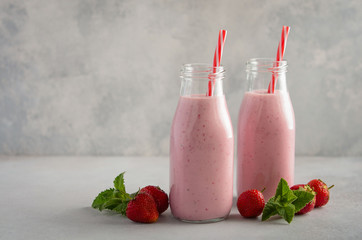 Strawberry milkshake on a gray concrete background, selective focus, copy space.