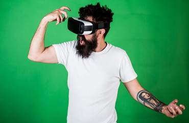 Virtual party concept. Hipster on shouting face having fun in virtual reality. Guy with head mounted display dance in virtual reality. Man with beard in VR glasses dancing, green background