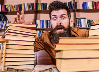 Man on shocked face between piles of books, while studying in library, bookshelves on background. Teacher or student with beard sits at table with glasses, defocused. Deadline concept.
