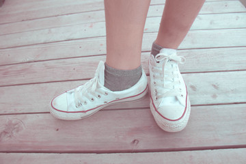 Feet in a pair of canvas shoes on wood floor, Canvas shoes walking on wooden