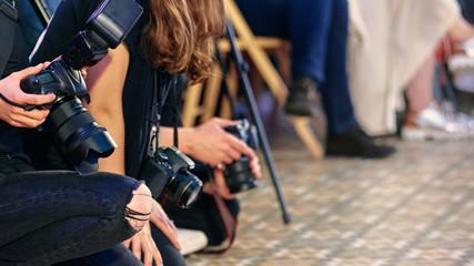 Crowd of journalists taking photo at fashion week presentation