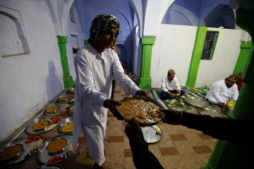 A Muslim man prepares plates of food for Iftar (breaking fast) meals inside a mosque during the holy month of Ramadan in Ahmedabad
