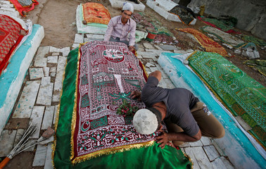 Muslim men pray at a grave at the shrine of sufi saint Shah-e-Alam during the holy month of Ramadan, in Ahmedabad