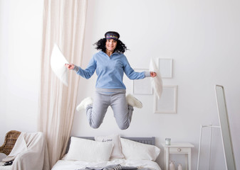 young woman jumping in pajamas on bed