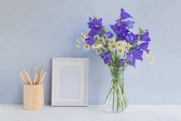 Mockup with a white frame and summer blue flowers
