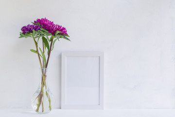 Mockup with a white frame and pink flower in a vase