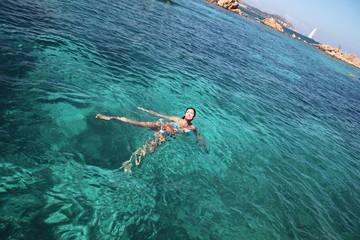 Donna abbronzata nuota in mare
