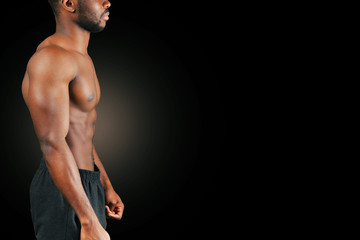Portrait of a strong afro-american man showing off his physique against black background.