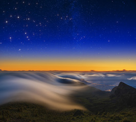 A magnificent spectacle of flowing clouds over the mountains at sunrise over Tenerife at night