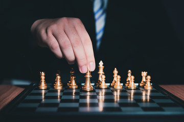 Businessman playing chess reaching golden queen piece moving.Business strategy and business leader concept.