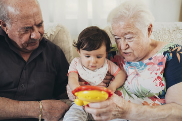 Great-grandparents sitting with girl at home