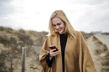 Laughing young woman looking at smartphone on the beach