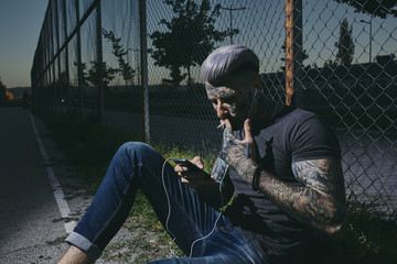 Tattooed young man with earbuds and smartphone smoking a cigarette at wire mesh fence
