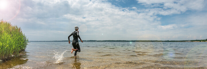 Woman in a wetsuit running into the water to swim, panorama