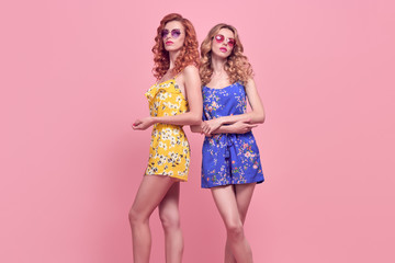 Wall Mural - Two Young Woman in Fashion pose. Trendy Floral Dress, Wavy Hairstyle. Glamour Sexy Blond Redhead Model in Stylish Sunglasses, Clutch. Playful Summer Slim Girl on Pink