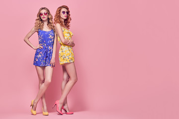 Wall Mural - Full-length portrait Two Young Woman in Fashion pose. Trendy Floral Dress, Wavy Hairstyle. Glamour Sexy Blond Redhead Model in Stylish Sunglasses. Playful Summer Girl on Pink