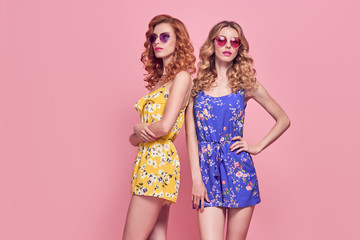 Wall Mural - Two Young Beautiful European girl Posing in Studio. Fashionable female Model, Wavy Hairstyle, Trendy Sunglasses. Sisters Twins in Stylish Glamour Summer Outfit. Gorgeous Woman