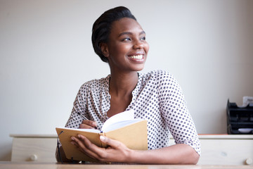 smiling young black woman writing in journal at home